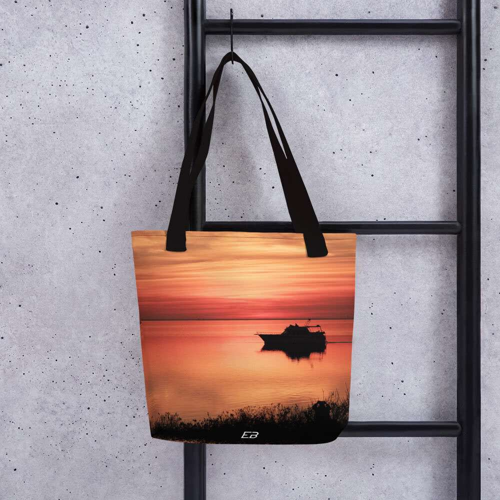 The Sunset By The Bay Tote Bag hanging from a ladder.