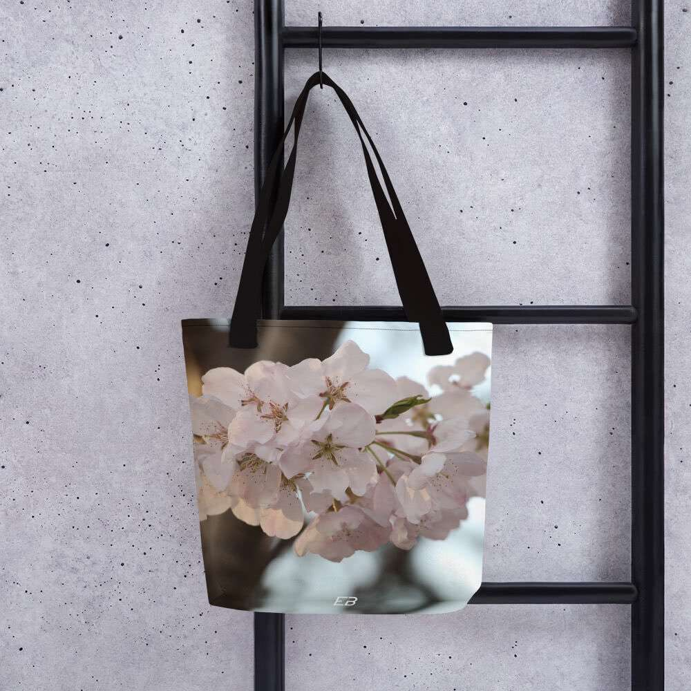 The White Cherry Blossom Tote Bag hanging from a ladder.